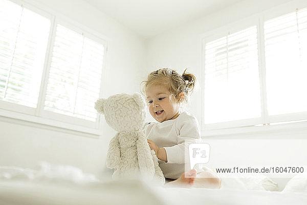 Kleinkind spielt auf dem Bett mit ihrem Teddybärenspielzeug
