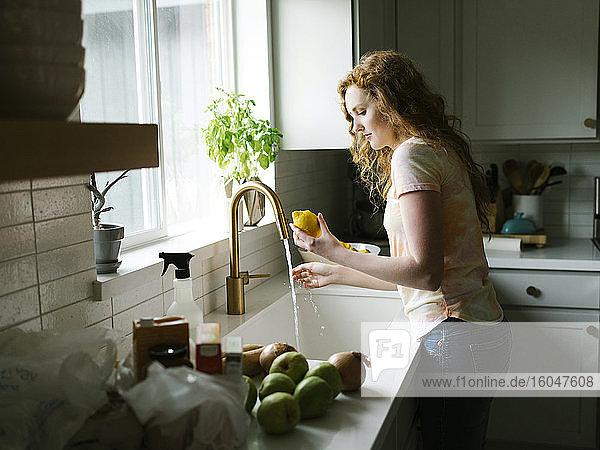 Frau wäscht Zitrone