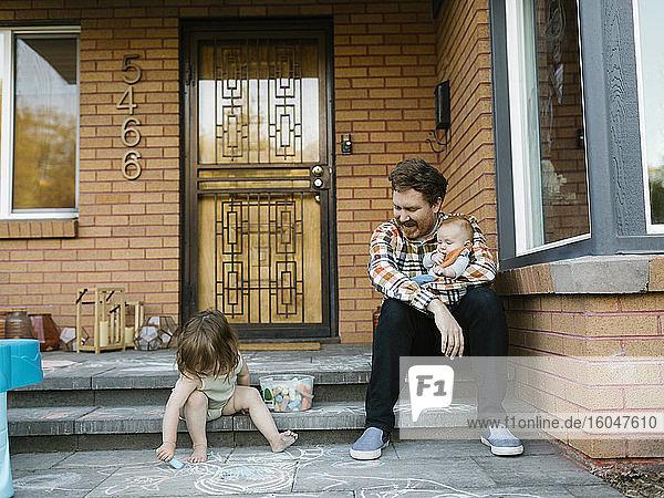 Vater mit Kindern auf der Veranda sitzend