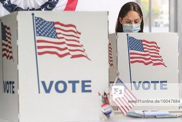Frau mit Gesichtsmaske bei der Abstimmung