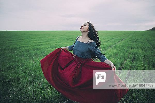 Young woman dancing in field