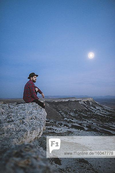 Ukraine  Krim  Wanderer sitzt am Rande einer steilen Klippe in der Nähe des White Mountain