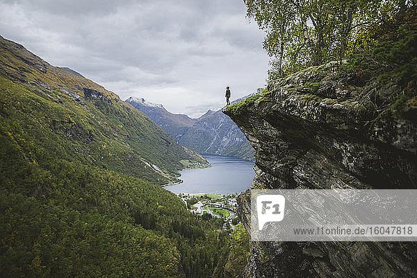 Norwegen  Geiranger  Mann steht am Rand einer Steilklippe über dem Geirangerfjord