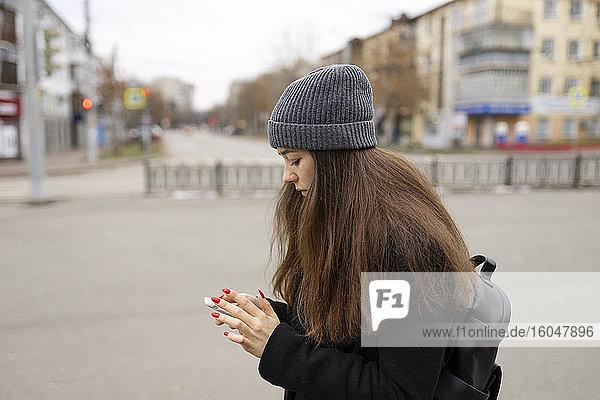 Russland  Tscheljabinsk  Junge Frau mit Smartphone in der Stadt