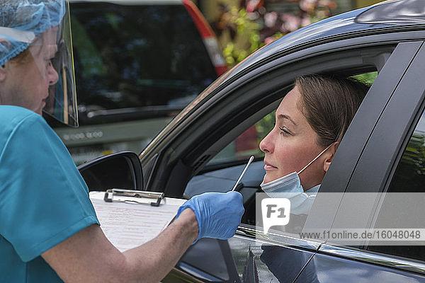 Frau im Auto beim Covid-19-Test