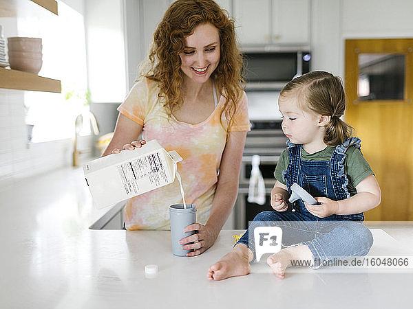 Mutter giesst Milch für die Tochter (2-3)