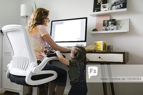 Mädchen (2-3) unterbricht Mutter bei der Arbeit von zu Hause aus