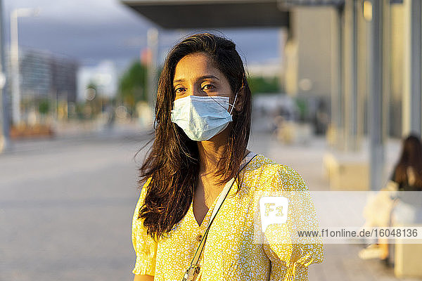 Young woman wearing face mask while standing on city street