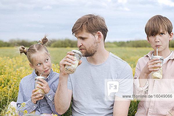 Family drinking lemonade at oilseed rape field