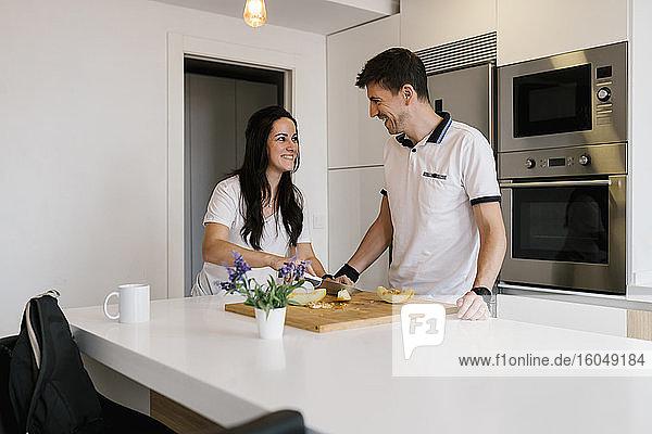 Lächelnde Frau  die einen Mann ansieht  während sie an einer Kücheninsel Obst schneidet