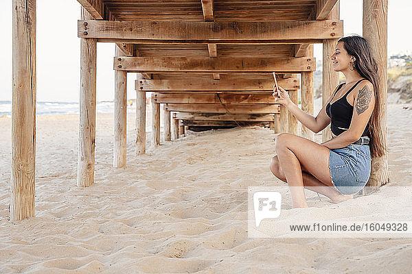 Happy teenage girl taking selfie through smart phone under pier at beach