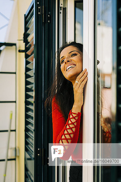 Cheerful young woman looking away while standing by door at home