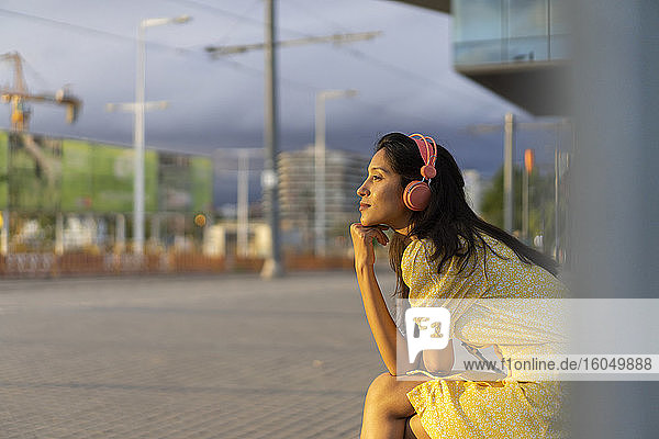 Thoughtful young woman listening music while sitting in city