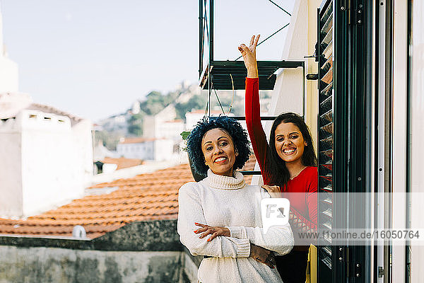 Cheerful female friends standing in balcony