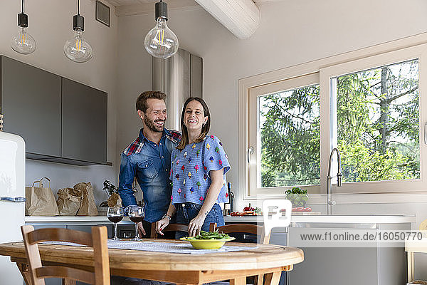 Smiling woman with man standing in kitchen at home
