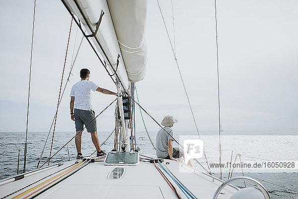 Freunde betrachten die Aussicht beim Segeln auf einem Segelboot gegen den Himmel Freunde betrachten die Aussicht beim Segeln auf einem Segelboot gegen den Himmel
