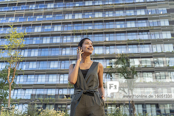 Smiling businesswoman talking over wireless earphone while standing against building in city