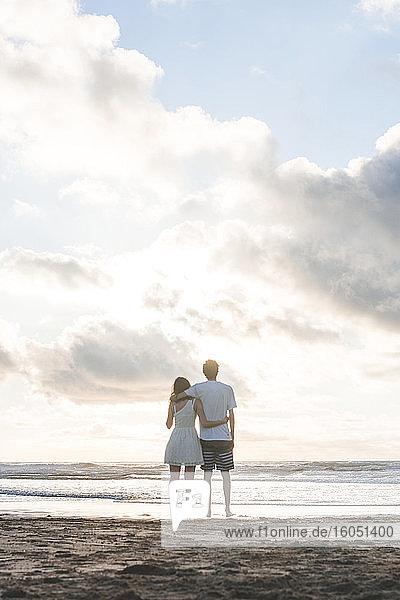 Verliebtes junges Paar  das sich in den Armen liegt und auf das Meer vor einem bewölkten Himmel blickt