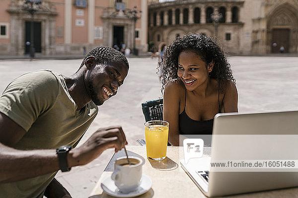 Glückliches Paar mit Laptop in einem Straßencafé