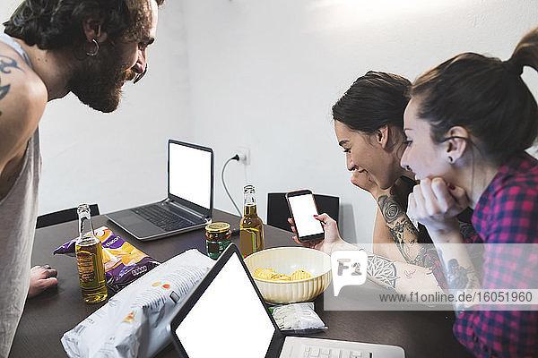 Frau zeigt Mitbewohnern ihr Smartphone auf dem Tisch zu Hause