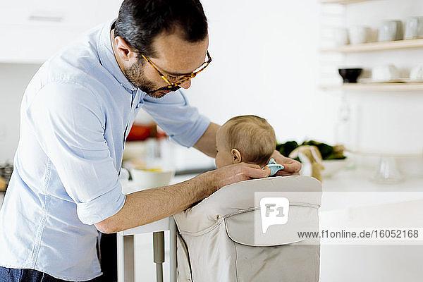 Vater mit Baby im hohen Haar zu Hause Vater mit Baby im hohen Haar zu Hause