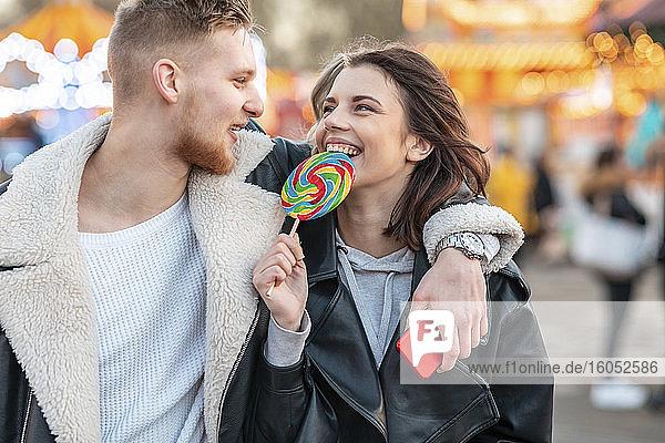 Glückliche Frau sieht ihren Freund an  während sie einen Lutscher im Vergnügungspark isst