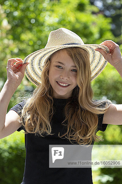 Close-up of smiling girl wearing hat while standing in park