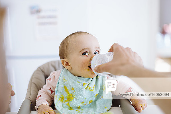 Father holding bottle with water for baby girl in high chair