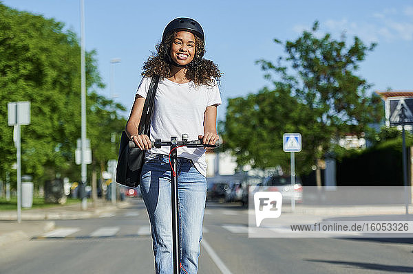 Happy woman riding electric push scooter in city during sunny day