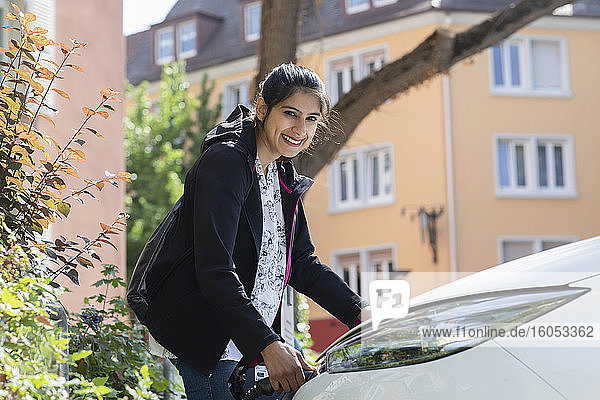 Smiling woman charging her electric car in city