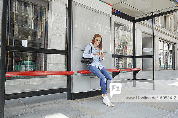 Junge Frau benutzt ihr Smartphone  während sie an einer Bushaltestelle in der Stadt wartet