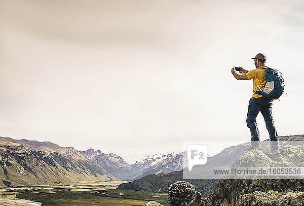 Mature man photographing mountains with smart phone against sky  Patagonia  Argentina