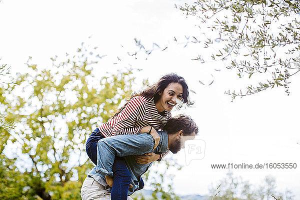 Verspielter Mann nimmt fröhliche Freundin gegen den Himmel huckepack