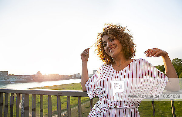 Smiling mid adult woman with curly hair leaning on railing against sky at sunset