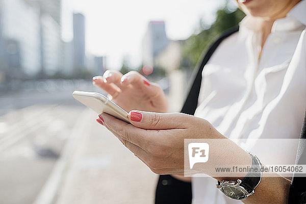 Nahaufnahme einer Geschäftsfrau  die in der Stadt ein Smartphone benutzt