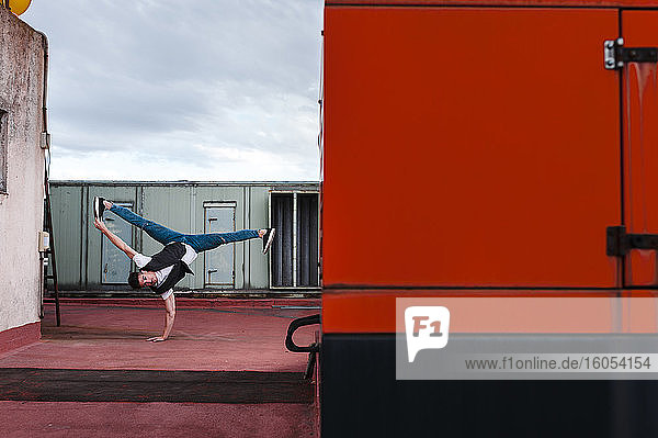 Male dancer breakdancing on abandoned building terrace against cloudy sky