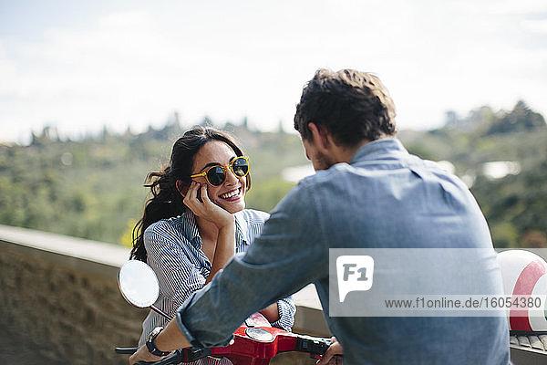 Glückliche Frau mit Sonnenbrille im Gespräch mit ihrem Freund auf einer Vespa sitzend Glückliche Frau mit Sonnenbrille im Gespräch mit ihrem Freund auf einer Vespa sitzend
