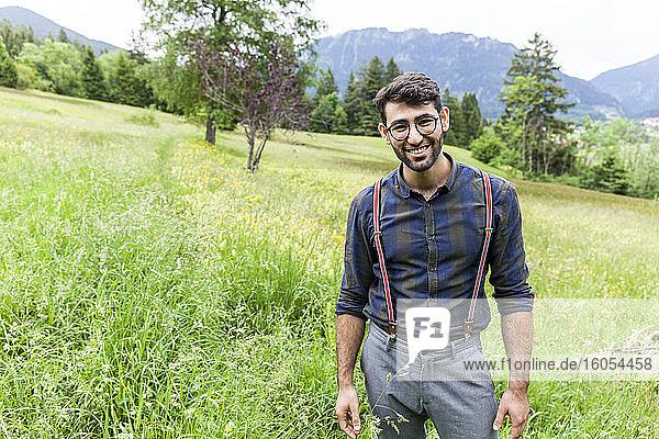 Porträt eines lächelnden jungen Mannes  der auf einer Wiese steht  Reichenwies  Oberammergau  Deutschland Porträt eines lächelnden jungen Mannes, der auf einer Wiese steht, Reichenwies, Oberammergau, Deutschland