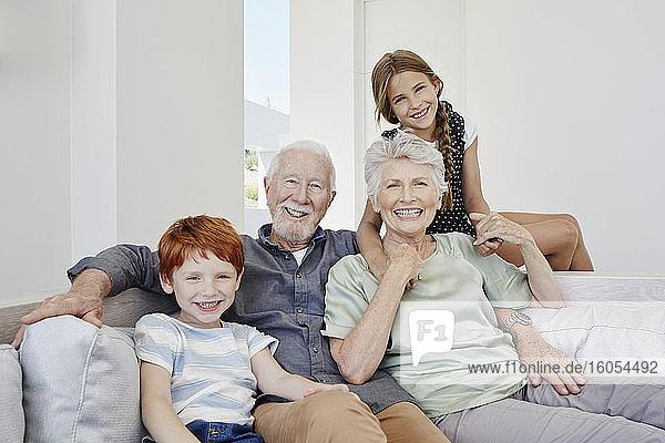 Porträt von glücklichen Großeltern mit Enkelkindern auf einer Couch in einer Villa
