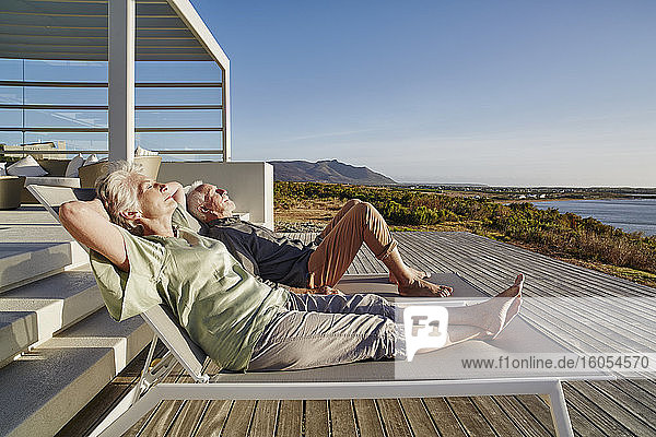 Senior couple lying on deck chairs at luxury beach house