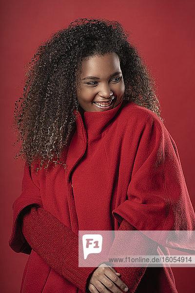 Lächelnde junge Frau in warmer Kleidung  die wegschaut  während sie vor einem roten Hintergrund steht