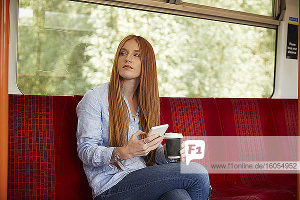 Thoughtful woman holding disposable glass and smart phone while sitting in train