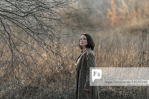 Beautiful mature woman standing by dead plant at forest