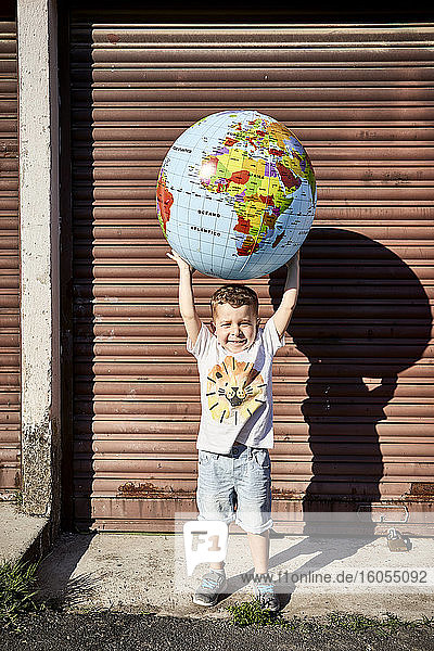 Boy carrying globe while standing on street against closed shutter during sunny day