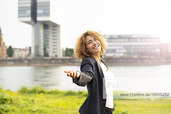Smiling businesswoman with arm outstretched standing against river in city