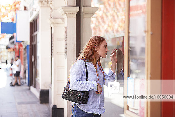 Young woman window shopping in city during sunny day