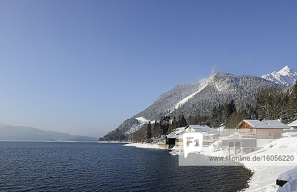 Germany  Bavaria  Houses on snow-covered shore of Lake Walchen