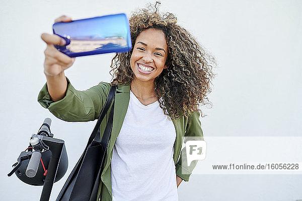Glückliche Frau nimmt Selfie durch Smartphone gegen weiße Wand Glückliche Frau nimmt Selfie durch Smartphone gegen weiße Wand