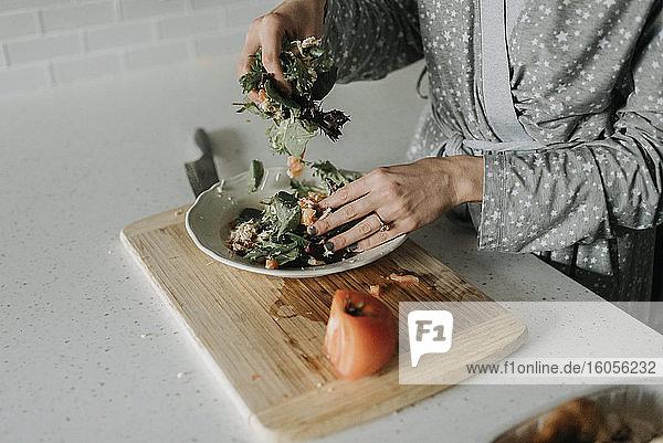 Nahaufnahme einer mittleren erwachsenen Frau  die zu Hause einen Salat auf einem Teller zubereitet