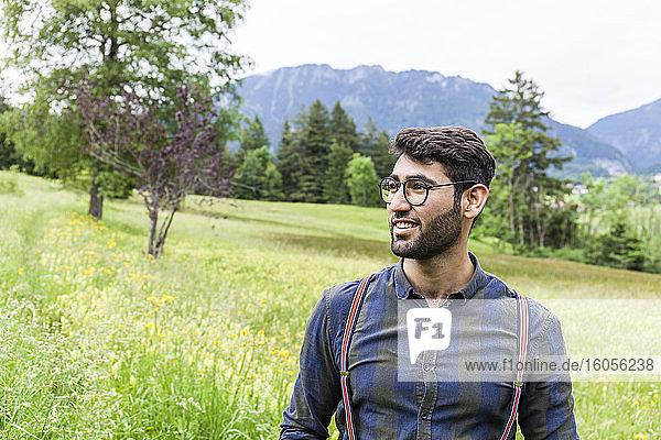 Porträt eines lächelnden jungen Mannes auf einer Wiese  Reichenwies  Oberammergau  Deutschland Porträt eines lächelnden jungen Mannes auf einer Wiese, Reichenwies, Oberammergau, Deutschland
